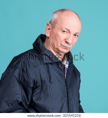 Thoughtful senior man on a blue background - stock photo