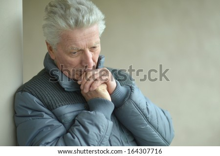 Thoughtful senior man portrait. Leaning against wall