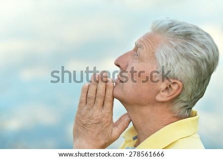 Thoughtful senior man prays in nature close-up - stock photo