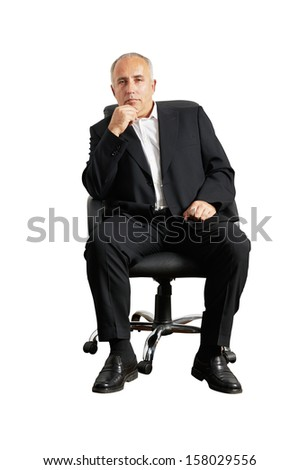 thoughtful senior man sitting on office chair and looking at camera - stock photo