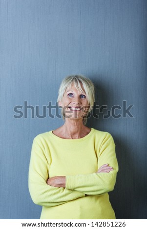 Thoughtful senior woman with arms crossed looking up against blue wall - stock photo