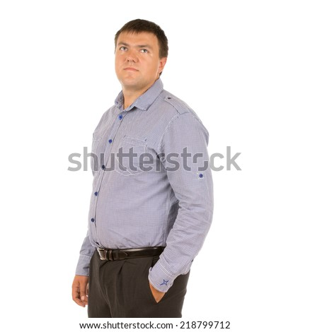 Thoughtful serious young man standing in a relaxed pose with his hand in his pocket staring pensively up into the air, isolated on white - stock photo