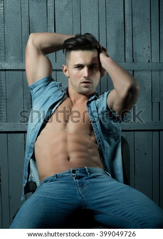 Thoughtful sexy sensual muscular young macho man with bare torso and stylish hair in jeans shirt indoor on wooden background, vertical picture - stock photo