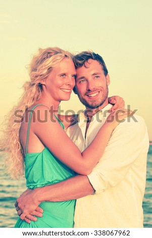 Thoughtful smiling young Caucasian couple are looking away. Partners are embracing each other while daydreaming. They are at beach. - stock photo