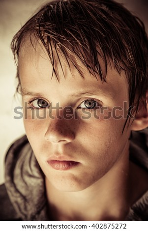 Thoughtful solemn young boy with wet hair looking at the camera with a speculative expression, close up head shot in shadow - stock photo