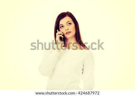 Thoughtful teen woman talking through a mobile phone - stock photo