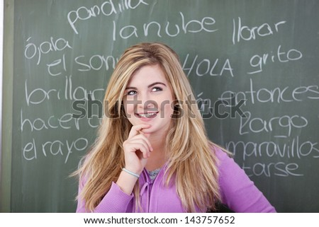 Thoughtful teenage girl with hand on chin against Spanish words written on blackboard - stock photo