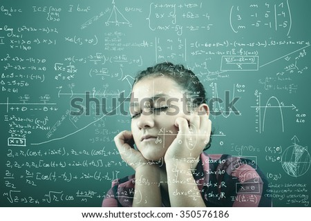 Thoughtful teenager near a blackboard with mathematical formulas - stock photo