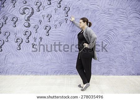 Thoughtful urban wall girl, feeling - stock photo