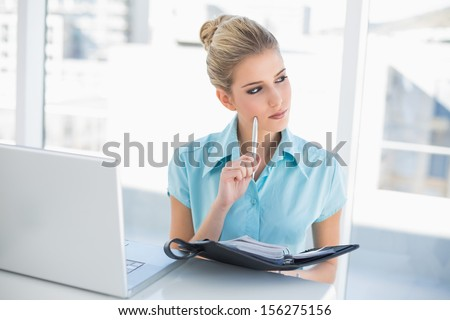 Thoughtful well dressed businesswoman writing on datebook in bright office - stock photo