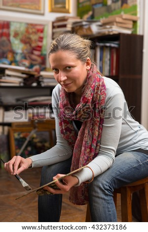 Thoughtful woman artist sitting in a gallery holding a colorful artists palette and paintbrush in her hand and looking at the camera - stock photo