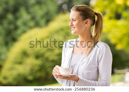 thoughtful woman holding cup of coffee outdoors