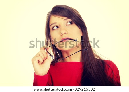 Thoughtful woman holding glasses looking up. - stock photo