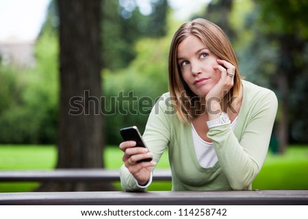 Thoughtful woman in park with smart phone - stock photo