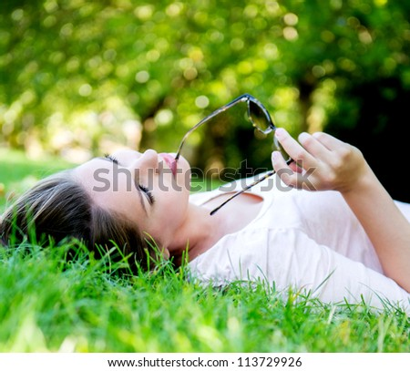 Thoughtful woman lying at the park looking up - stock photo