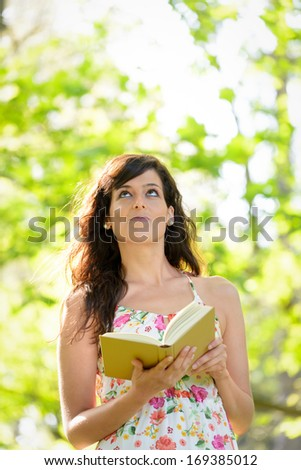 Thoughtful woman reading interesting book and having an idea. Brunette girl looking up in park. - stock photo