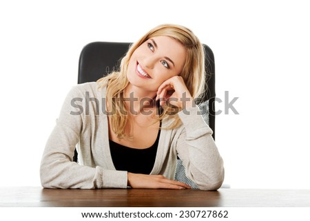 Thoughtful woman sitting at the desk touching chin.