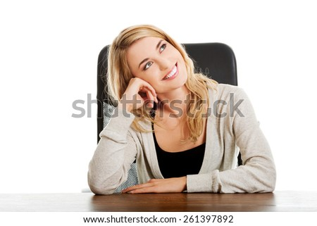 Thoughtful woman sitting at the desk touching chin. - stock photo