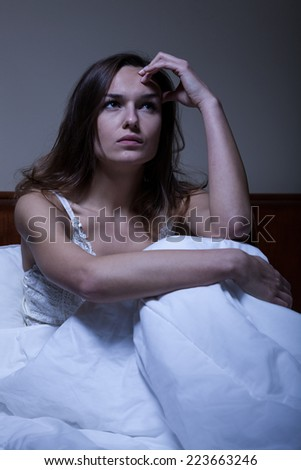 Thoughtful woman sitting in bed at night - stock photo