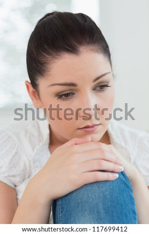 Thoughtful woman sitting on the couch in a living room and looking sad