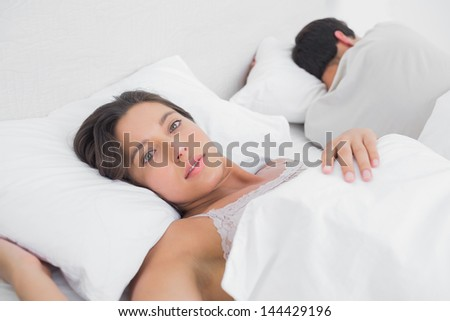 Thoughtful woman sleeping in bed next to her partner