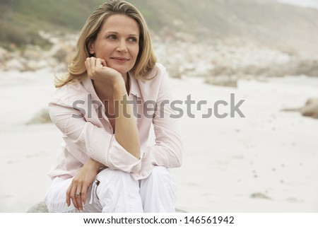 Thoughtful woman smiling while relaxing at beach