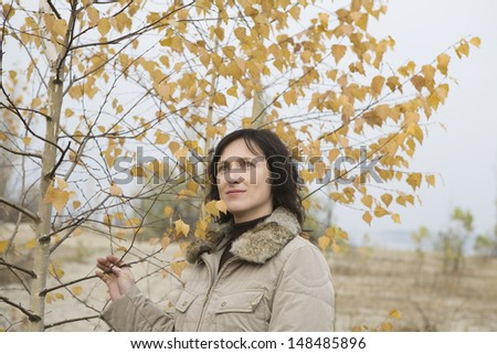 Thoughtful woman standing besides tree in field - stock photo