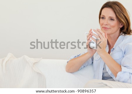 Thoughtful woman with cup of coffee on the sofa - stock photo