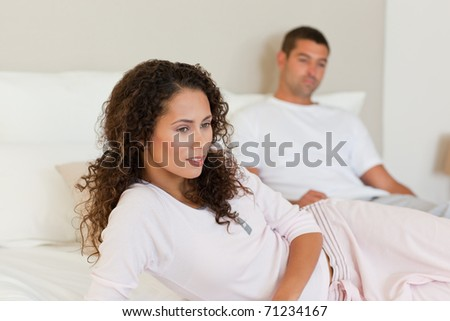 Thoughtful woman with her husband on the bed - stock photo