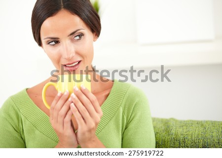 Thoughtful woman with pulled back hair holding a yellow mug while looking away - copy space