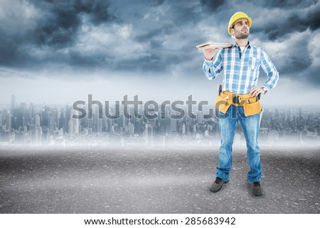 Thoughtful worker carrying wooden planks against road - stock photo