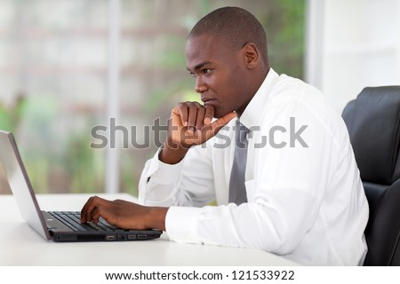 thoughtful young african american businessman working on laptop computer - stock photo