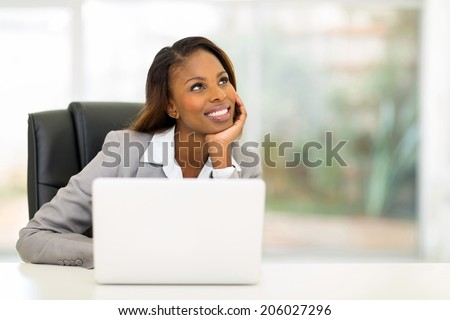 thoughtful young african businesswoman looking up - stock photo