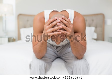 Thoughtful young bald man sitting with head in hands on bed at home - stock photo