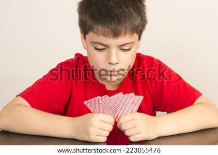 Thoughtful young boy playing cards - stock photo