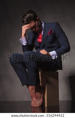 Thoughtful young business man sitting on a wood box while holding his hand to the forehead thinking.