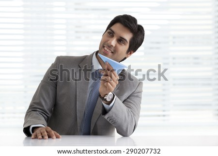 Thoughtful young businessman holding paper plane at his desk - stock photo