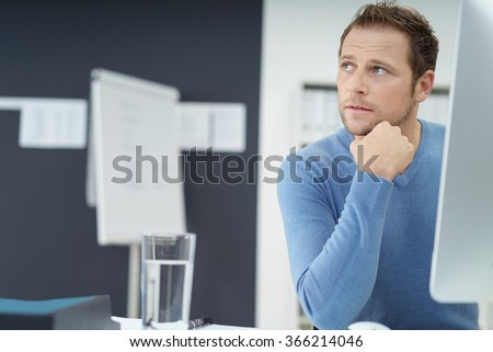 Thoughtful young businessman sitting at a desk in the office watching something to the left side of the frame with an engrossed expression - stock photo