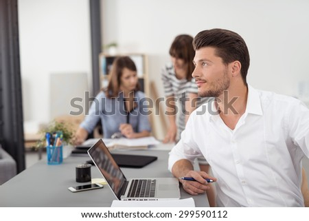 Thoughtful Young Businessman Sitting at the Boardroom with Laptop Computer and Looking Into Distance with Serious Facial Expression. - stock photo
