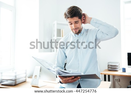 Thoughtful young businessman standing and looking through documents in office