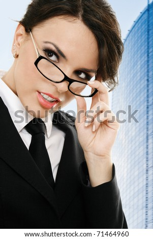 Thoughtful young businesswoman against blue office building - stock photo