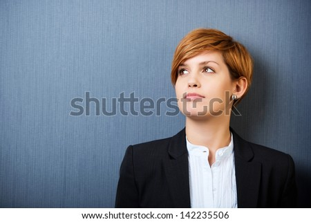 Thoughtful young businesswoman looking away isolated over blue background - stock photo