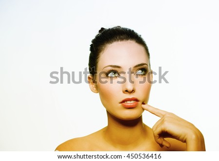 Thoughtful young businesswoman with finger on chin looking up against white background. - stock photo