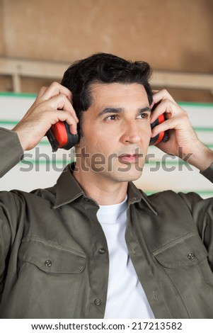 Thoughtful young carpenter wearing ear protectors in workshop - stock photo