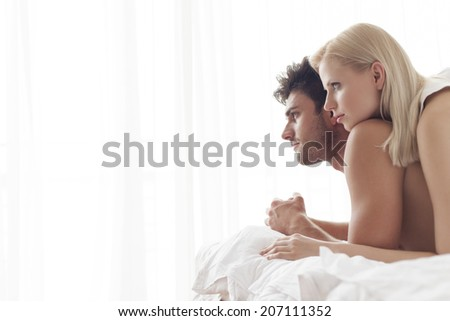 Thoughtful young couple in bed - stock photo