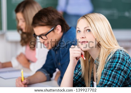 Thoughtful young female student sitting with classmates at classroom desk - stock photo