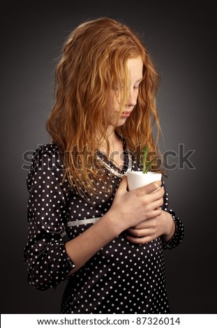 Thoughtful young girl holding small plant
