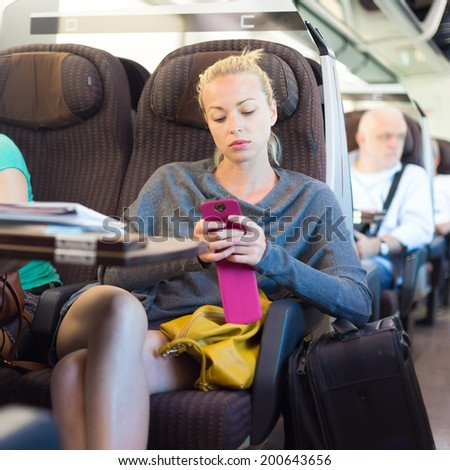 Thoughtful young lady surfing online on smartphone while traveling by train.