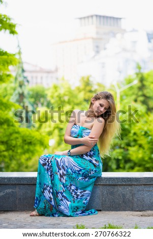 Thoughtful young lady wearing blue dress posing outdoors - stock photo