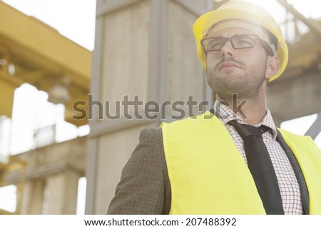 Thoughtful young male architect in protective wear at construction site - stock photo